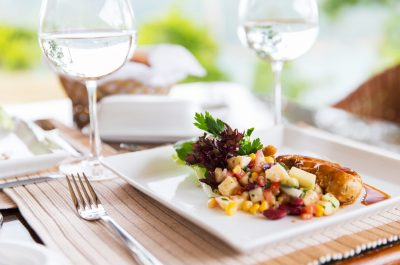 food, cooking and eating concept - close up of meat dish with garnish and water glasses on table at restaurant or home